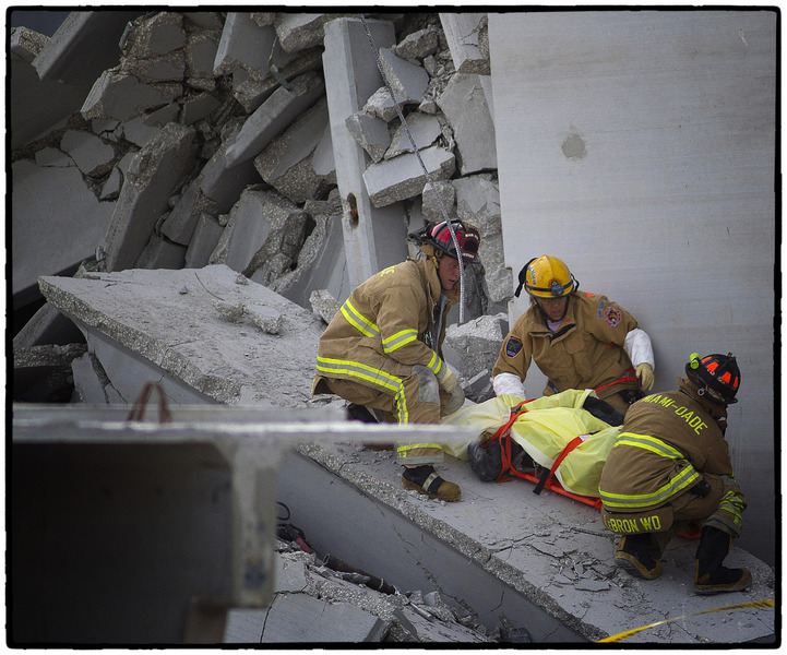 Rescue officials carry a victim of a building collapse out of the rubble : The Aftermath Sessions : Oklahoma City Editorial and Documentary Photographer